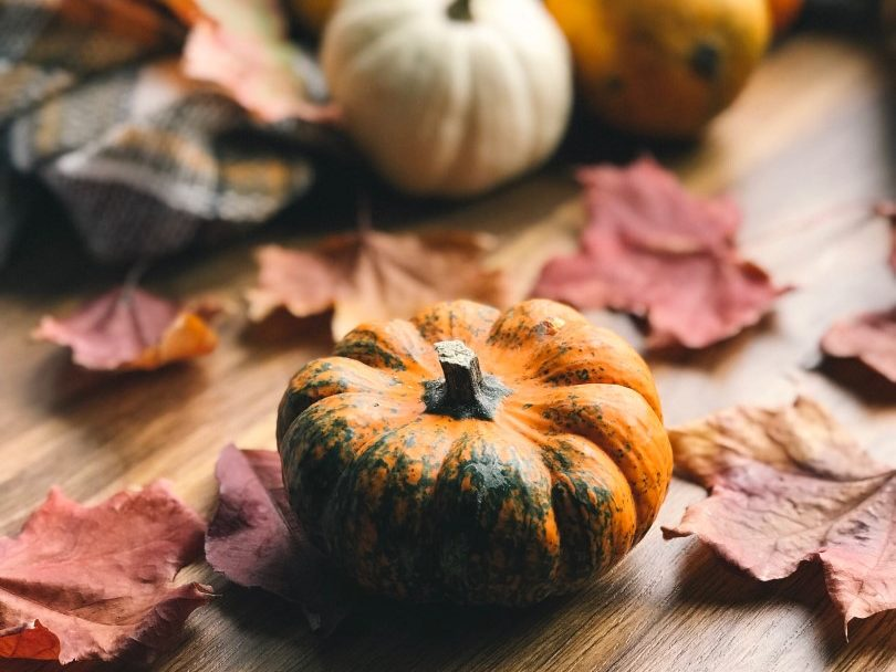 Small pumpkins and leaves on a wood surface.